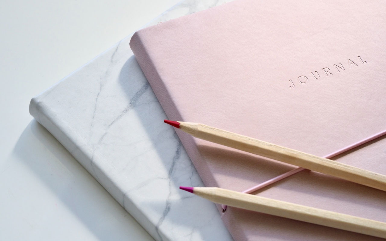 Two journals sit against a blank surface, with 2 colored pencils on top. Journaling can help you learn how to visualize effectively.