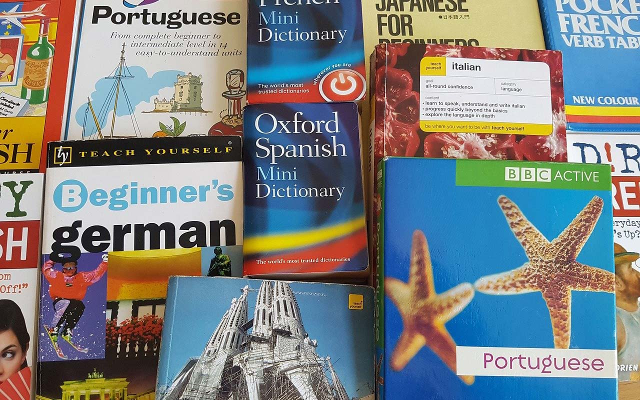 A stack of language learning books spread out on a table. Learning how to speak fluently can be overwhelming if you use too many materials.