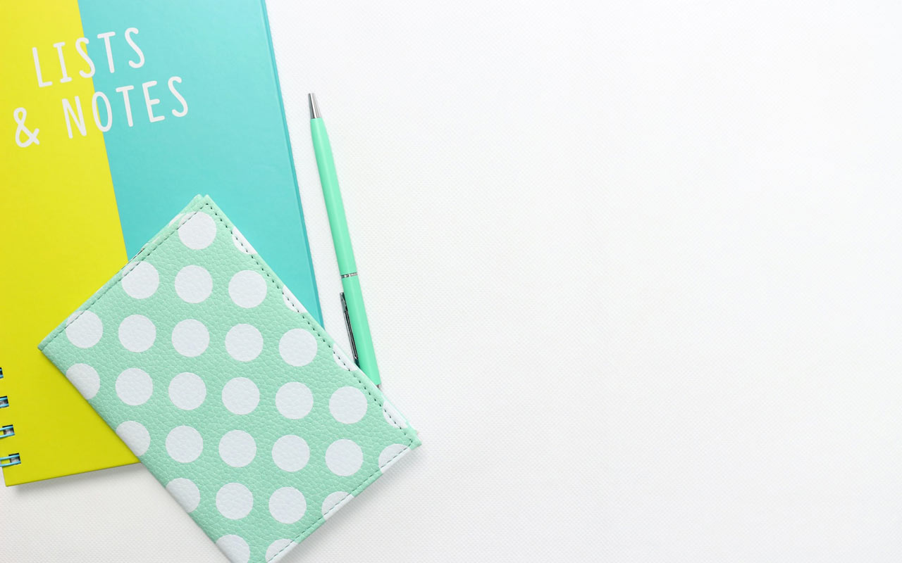 "A yellow and blue notebook with ""Lists & Notes"" lettered on the cover, as well as a sea-foam green journal and pen."