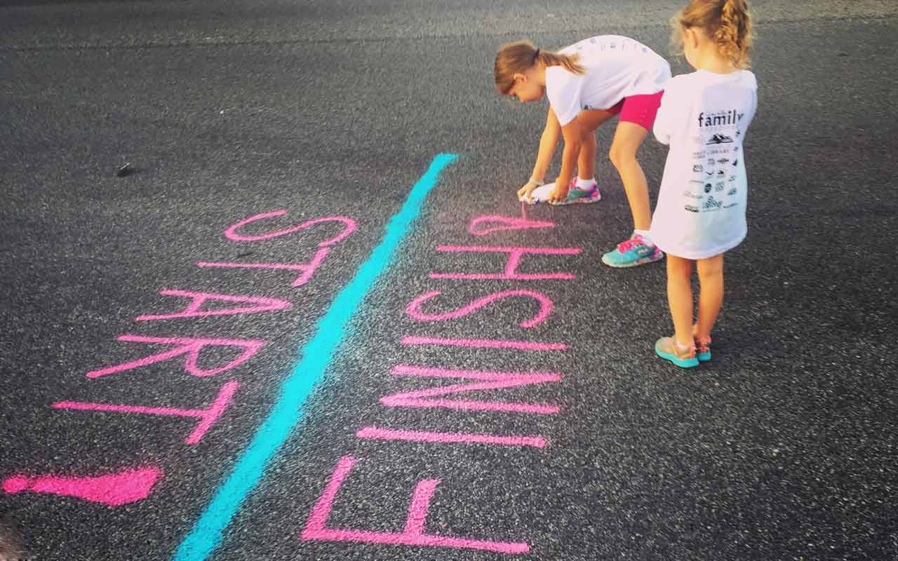 Young girls paint a start/finish line on the pavement.