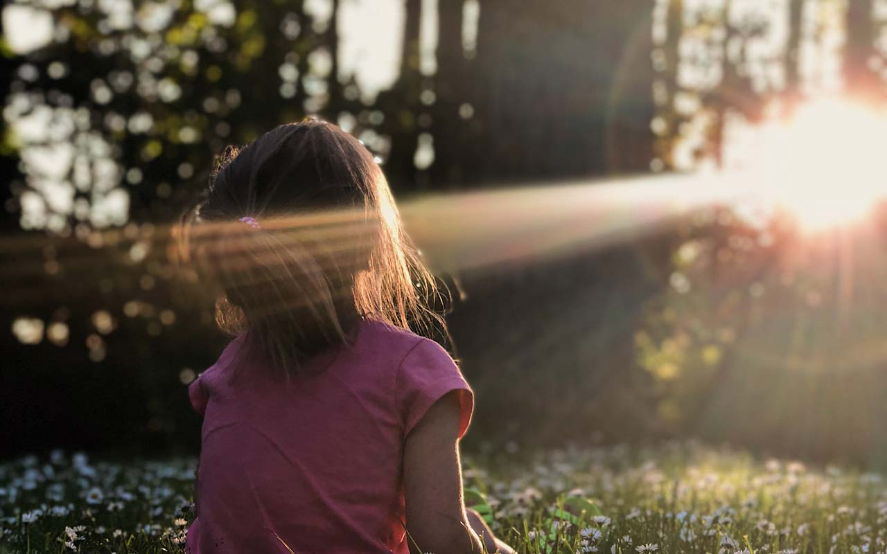 A young girl sits in a beam of light in nature. Choosing a natural environment to meditate in can help you focus.