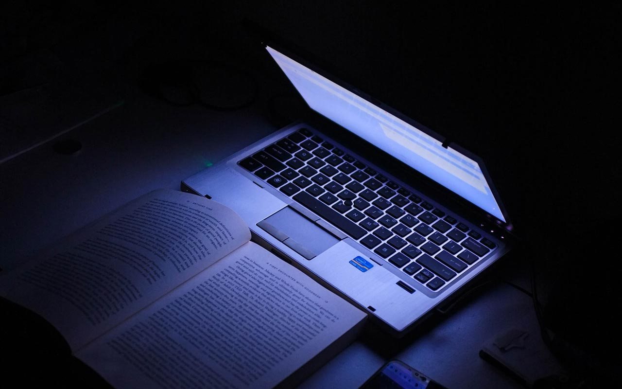 A laptop illuminates a book in a dark room.