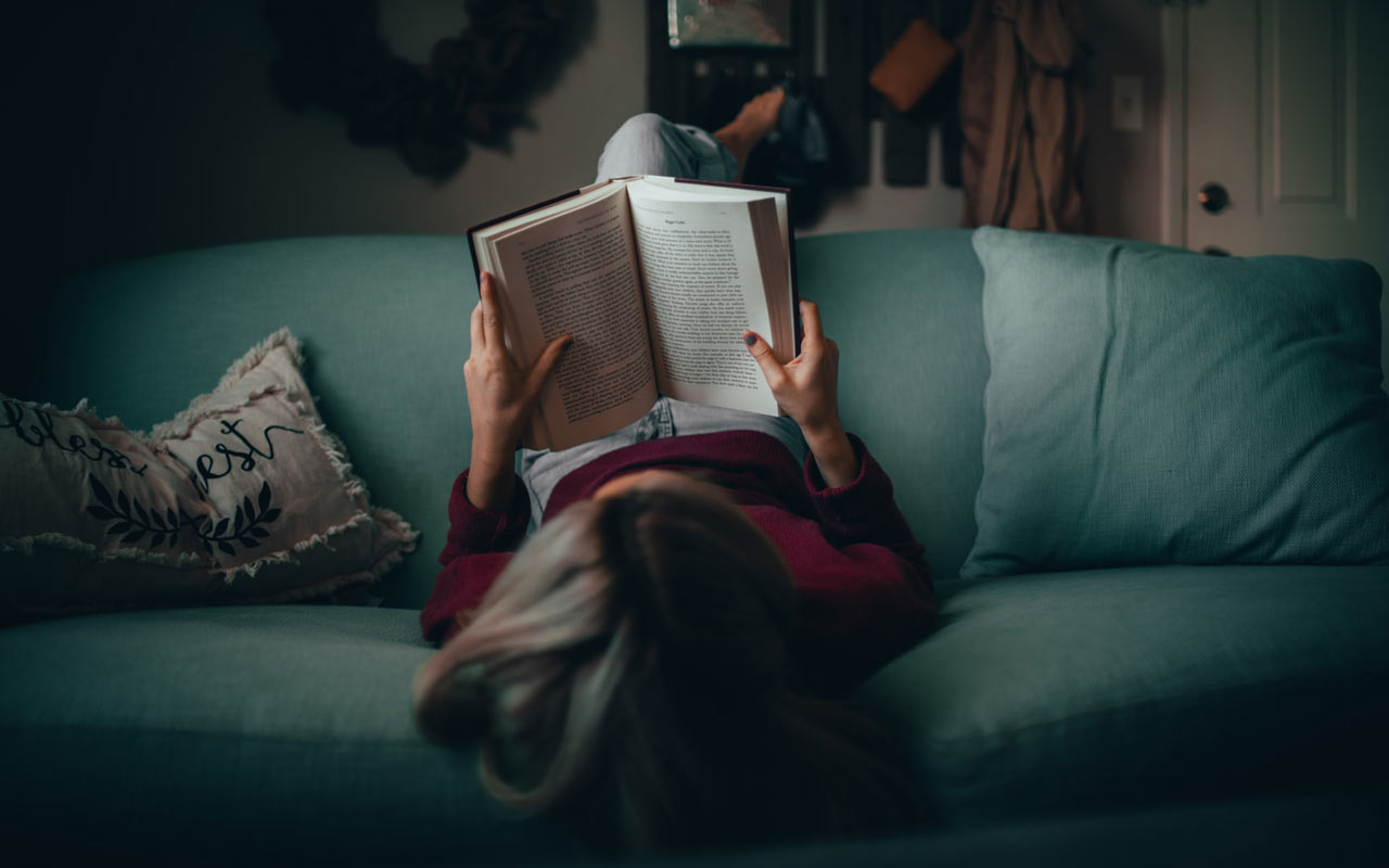 A person reads on a couch with their legs up over the back of the couch.
