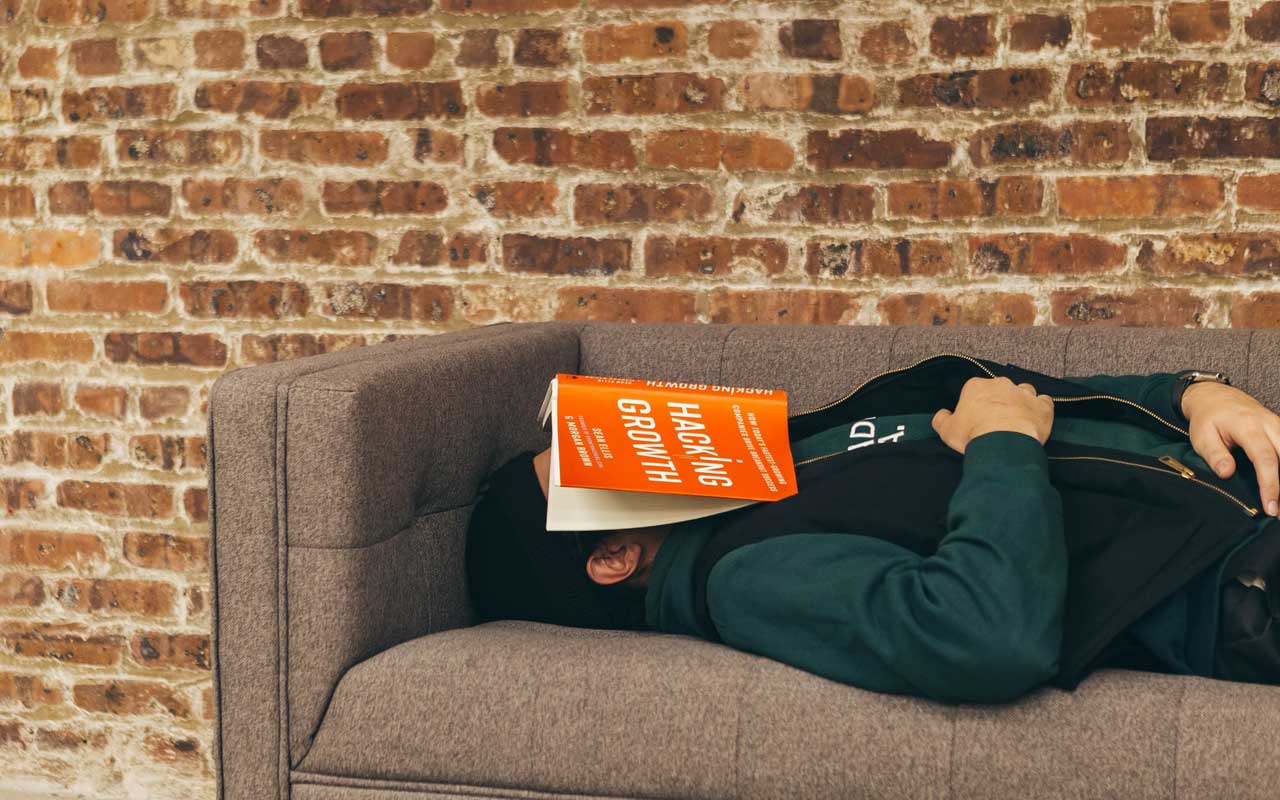 A person naps on a couch with a book over their face.