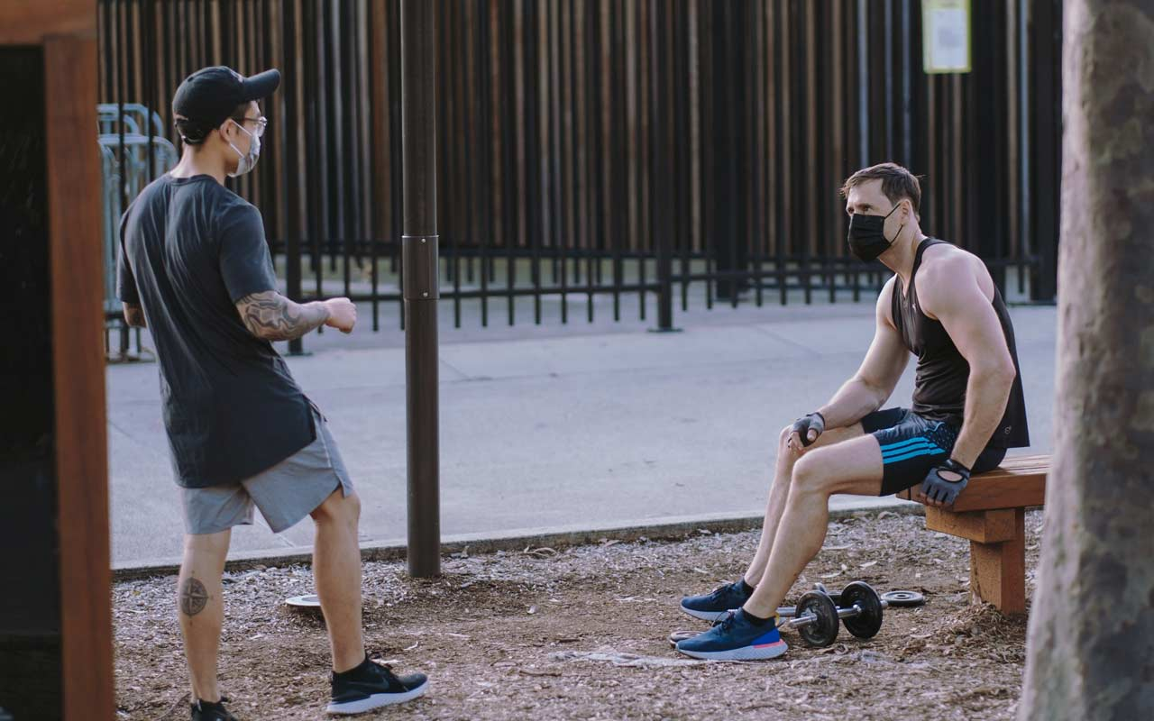 Two men wearing masks stand outside socializing while one man works out.