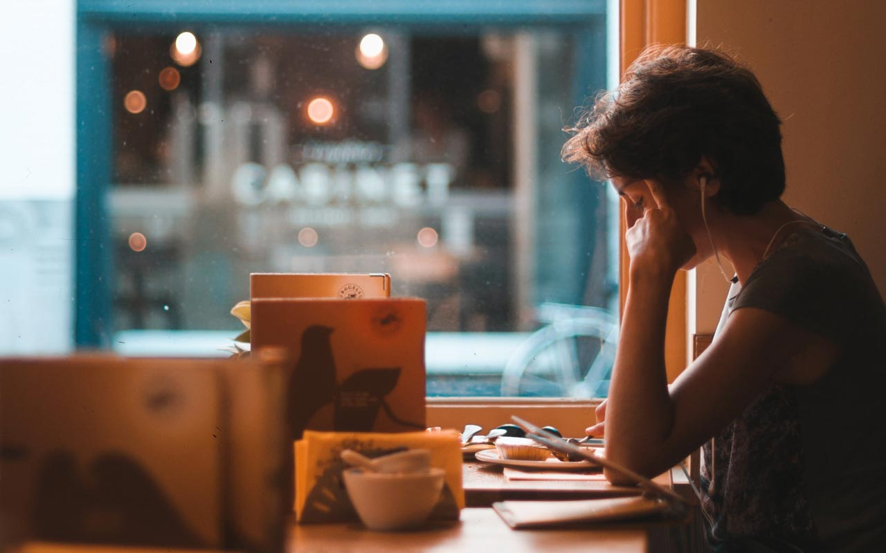 A person sits at a cafe table studying a stack of papers.