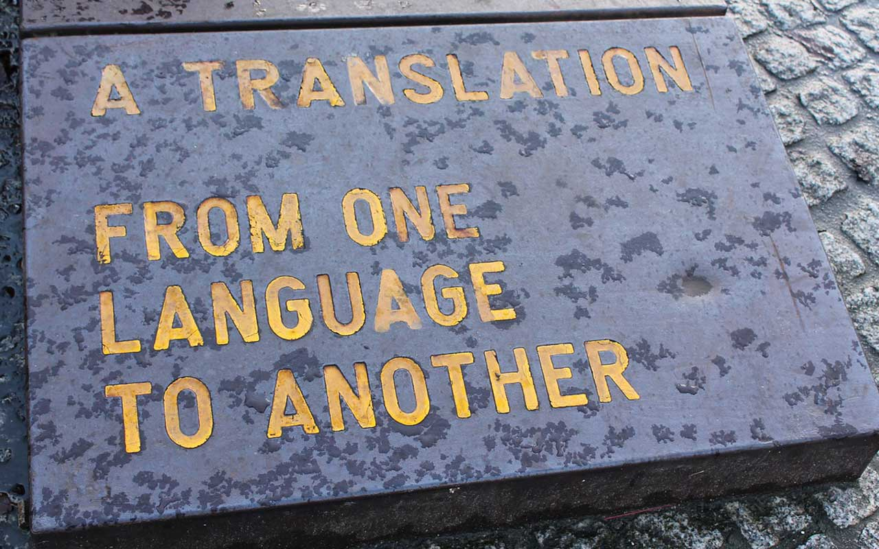 """A gray stone laid in the ground with yellow text that reads, """"A translation from one language to another."""""""