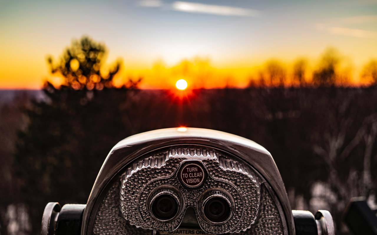 A tower viewer (binoculars on a stand) overlooks an out of focus horizon at sunset.