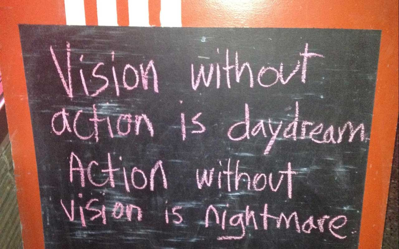 "A chalkboard sign outside a cafe reads, ""Vision without action is daydream. Action without vision is nightmare."""