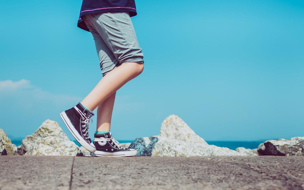 A person wearing Chuck Taylors walks along a concrete sidewalk, against the backdrop of a blue sky.