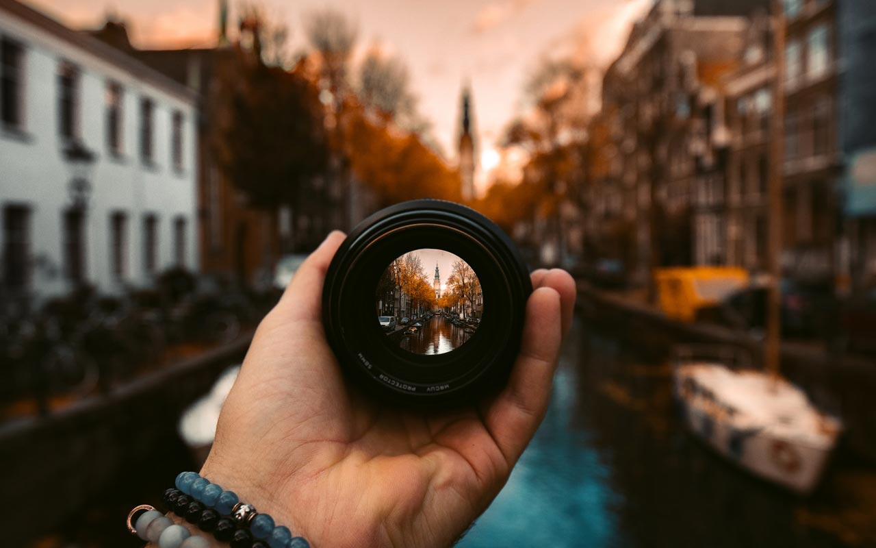 A person holds a camera lens. The focus shows a canal in Amsterdam, with the rest of the photo in soft focus.