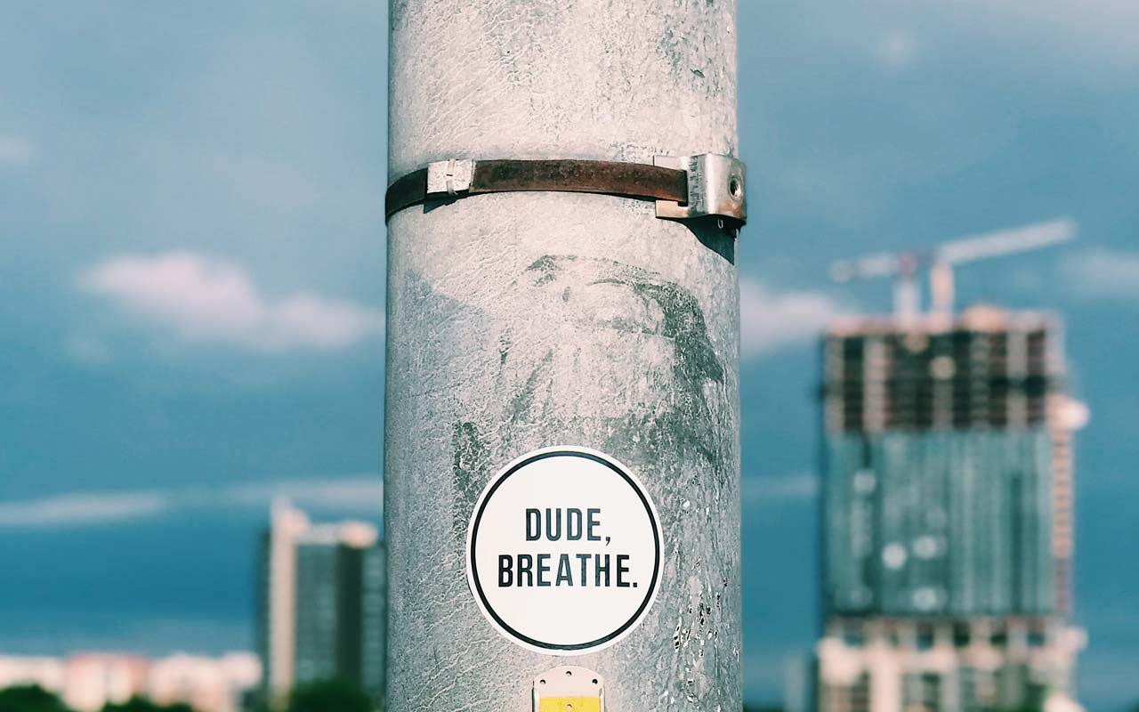 "A sticker on a pole (overlooking a cityscape) reads ""Dude, breathe."""