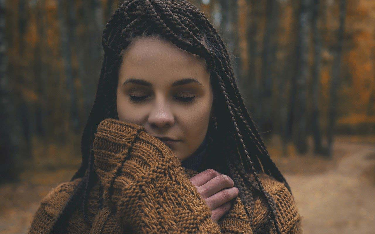 A woman with braids stands on a forest path in a chunky sweater with her eyes closed.