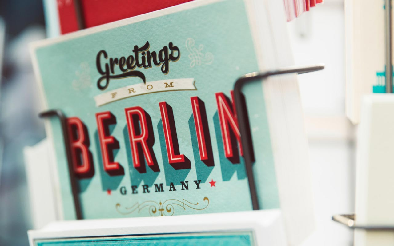 "A postcard in a rack reads, ""Greetings from Berlin."" German is one of the top business languages."