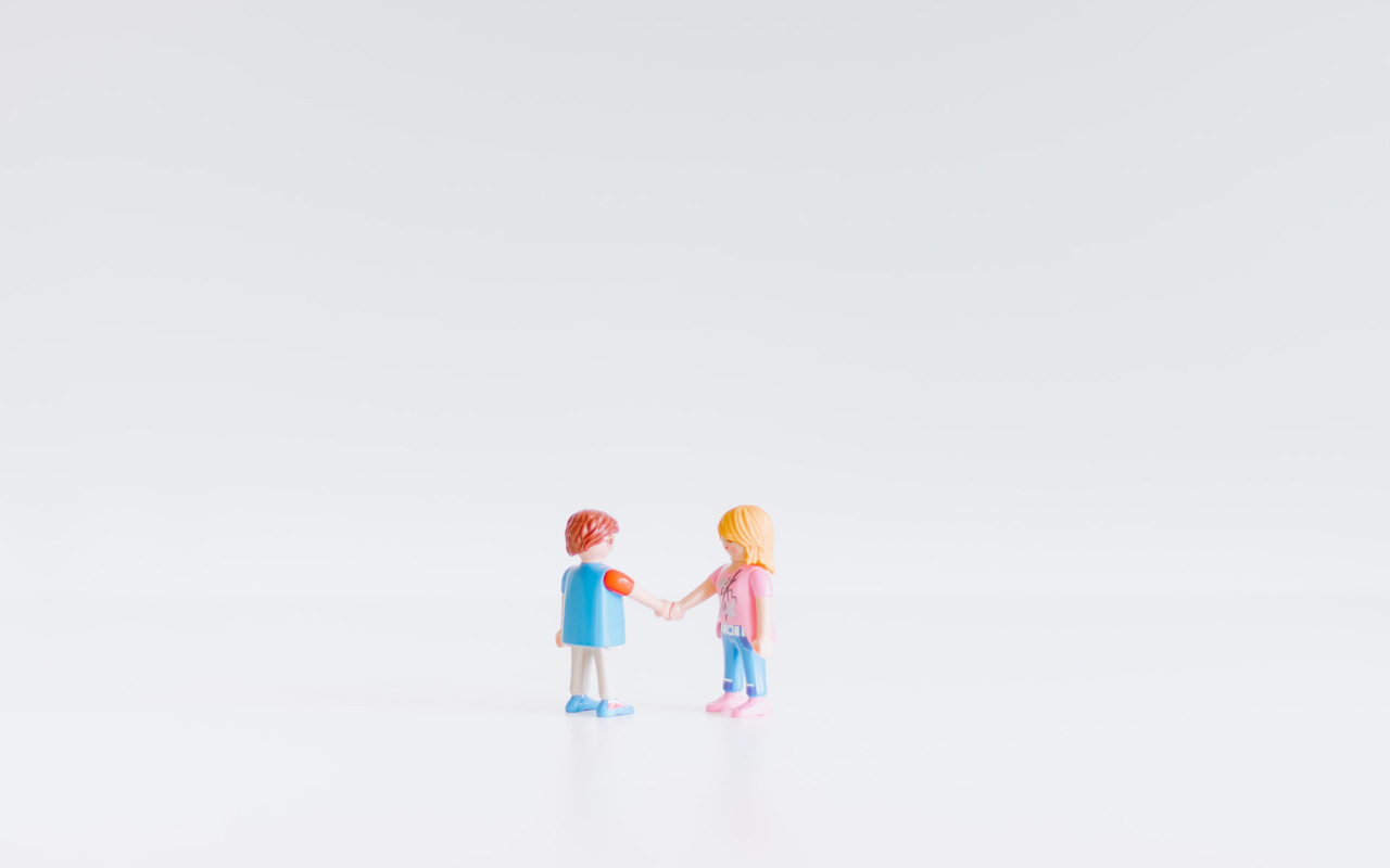 Two figurines shake hands. Use this step to assess your client base and workforce to determine your best language to learn for business.