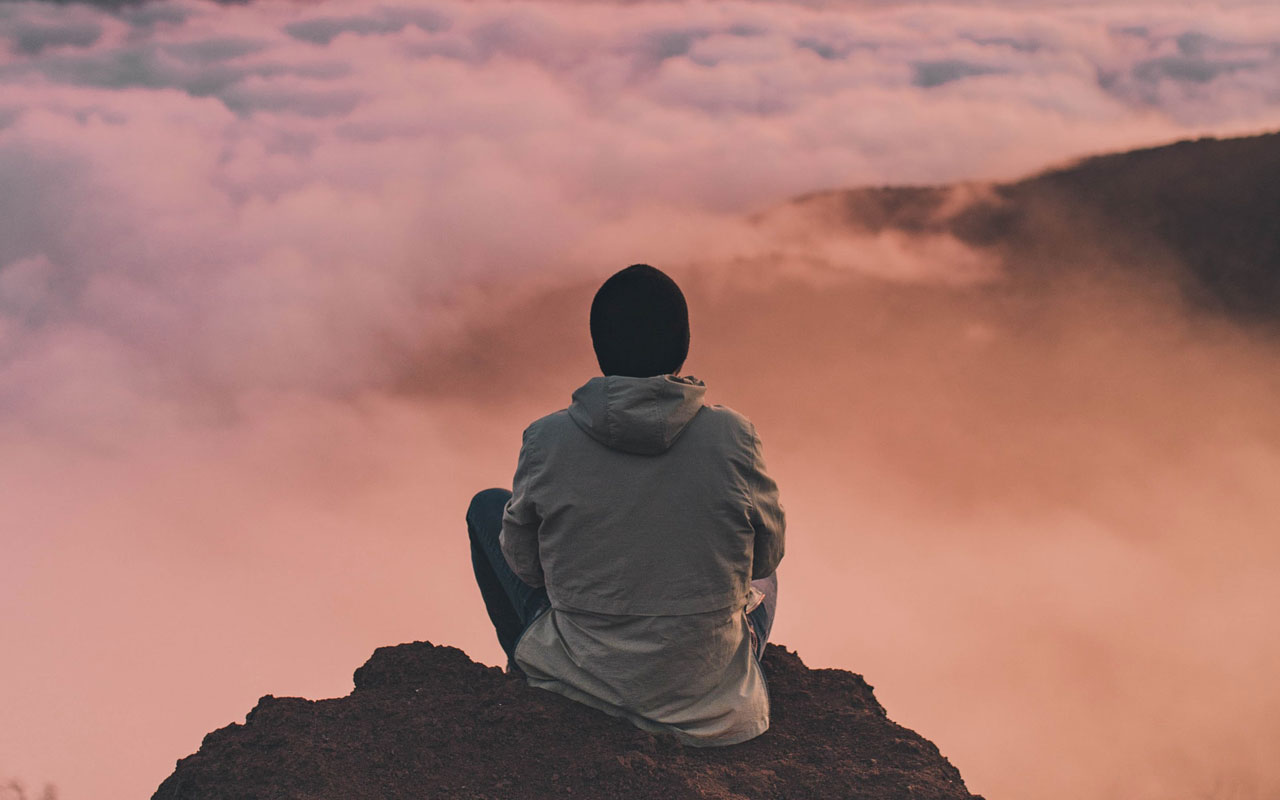 A person in a coat and winter hat sits at the top of a mountain at sunset, overlooking the clouds below.