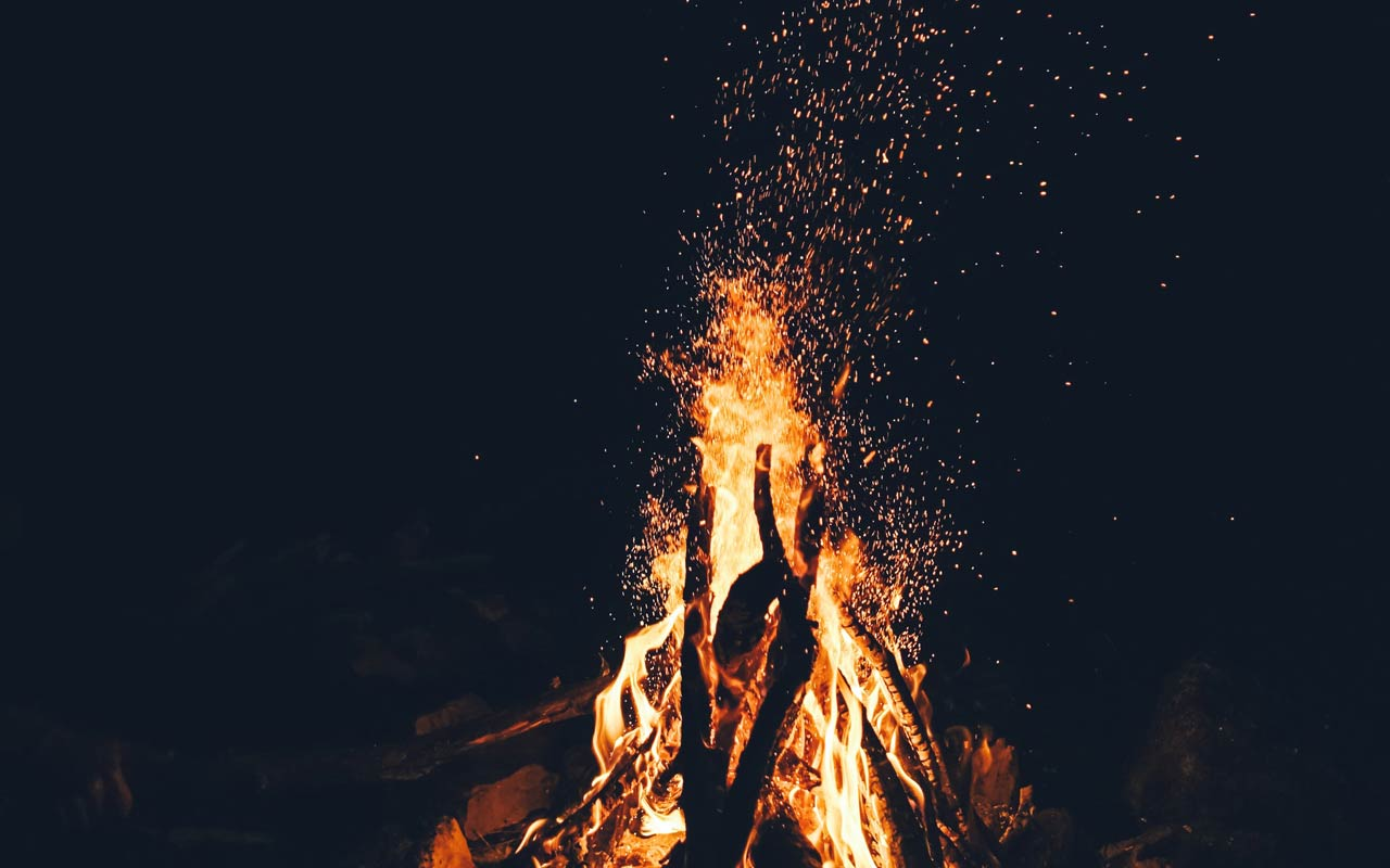 A bonfire burns in the darkness.