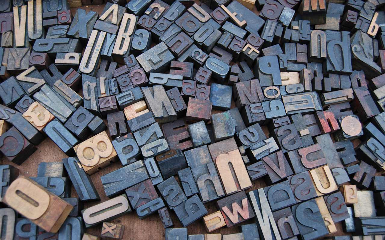 A series of print blocks from a printing press, with numbers and letters in many different shapes and sizes.