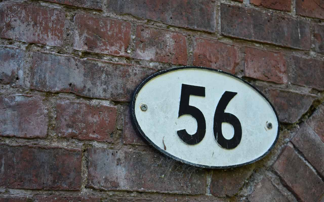 "A house number ""56"" in white with black numbers against a brick wall. 56 was the second number in this example of an N-back Test."