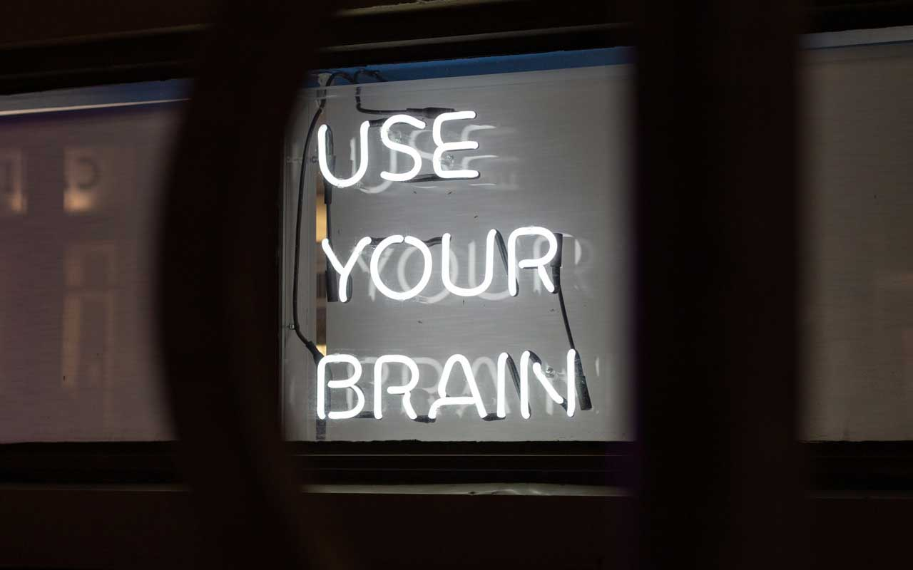"A white neon sign against a black background reads ""USE YOUR BRAIN."""