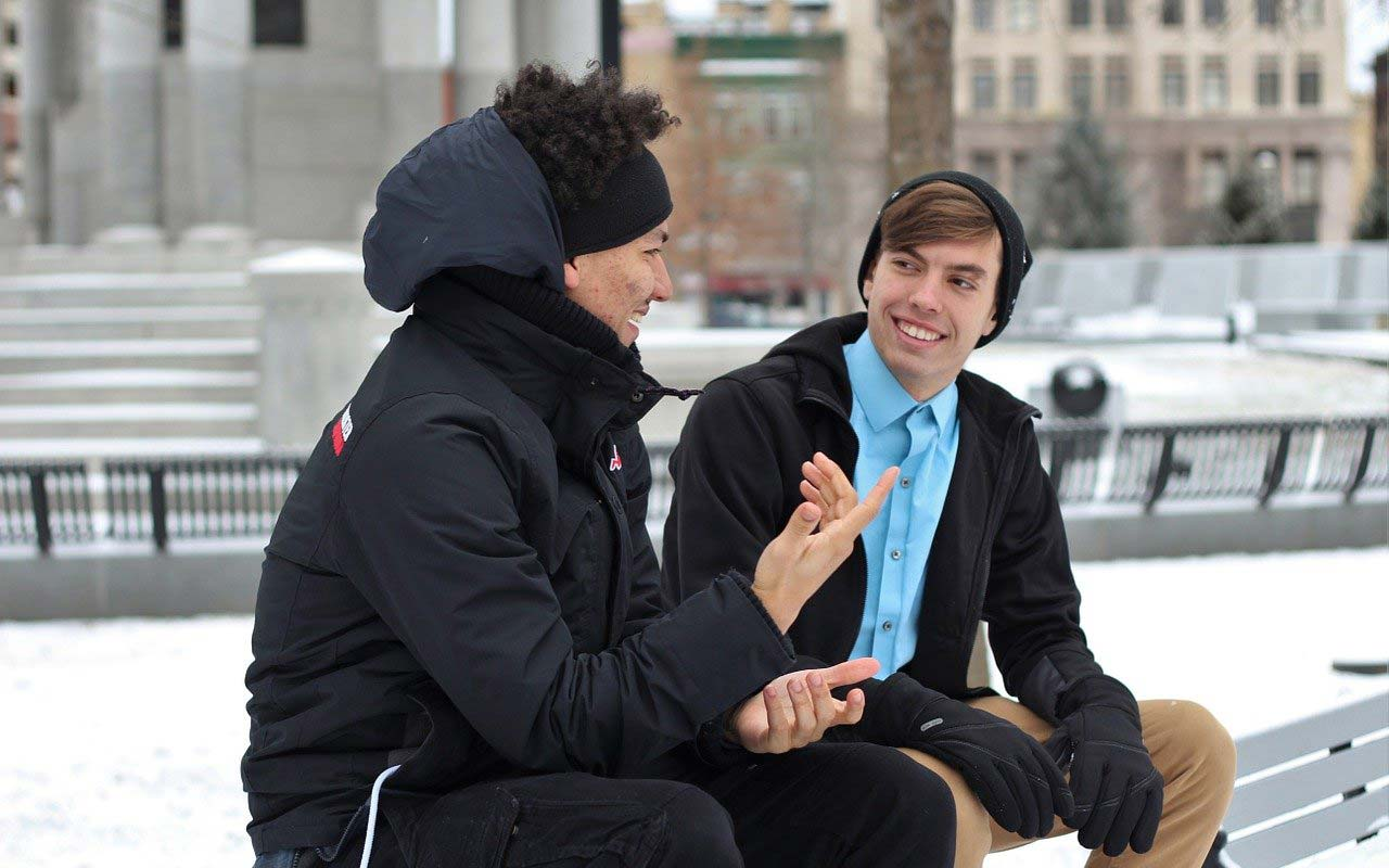 Two young men sit outside on a bench, conversing. One is smiling and listening while the other talks and uses hand gestures.