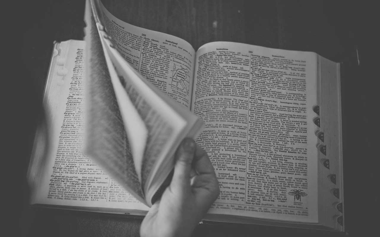 A person flips through the pages of a large dictionary. Having a large vocabulary can help you think faster.