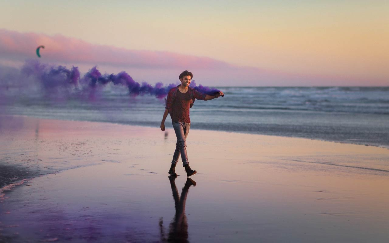 A person walks along a beach at sunset.