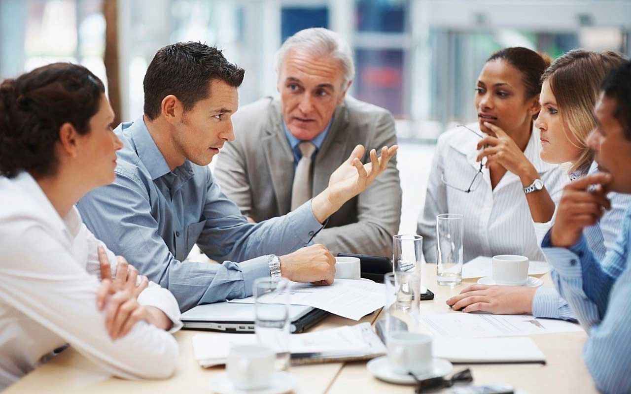 A racially and gender-diverse group of people dressed in business attire sit around a table, deep in discussion.