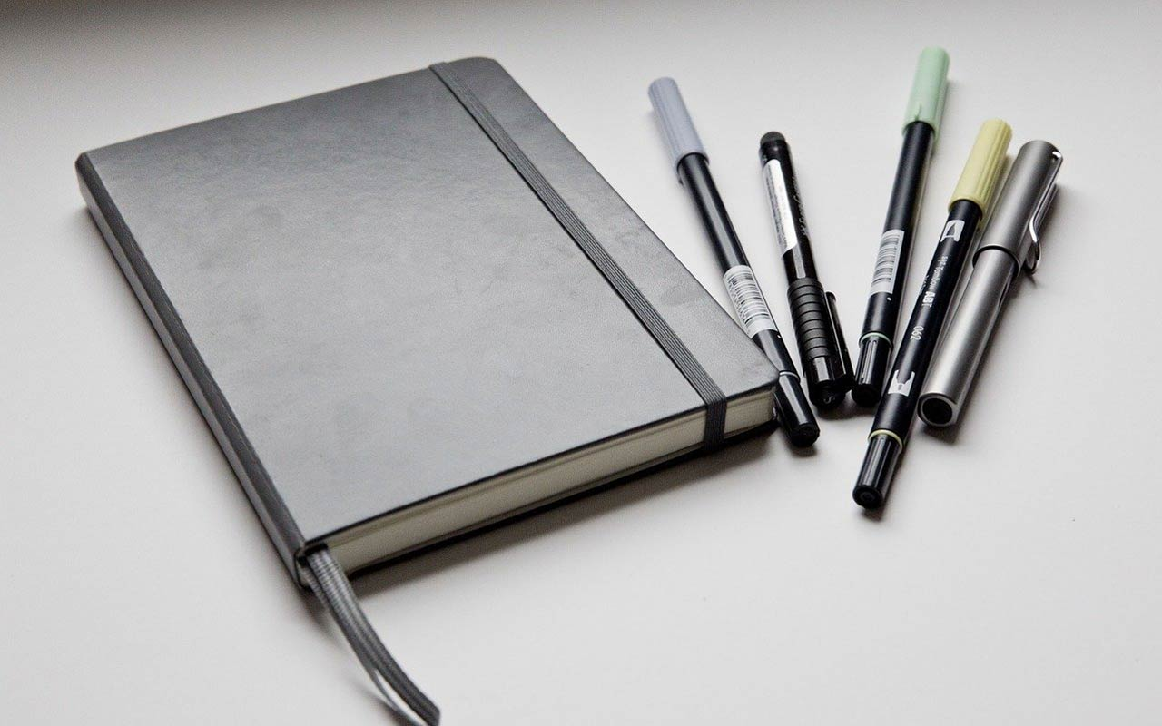 A black day planner sits on a table with a handful of pens. Writing out your daily plan in Spanish is a good way to practice your language learning.