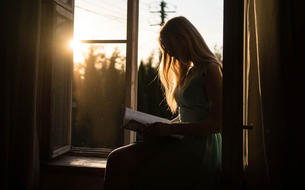 At sunset, a woman sits near an open window with a book.