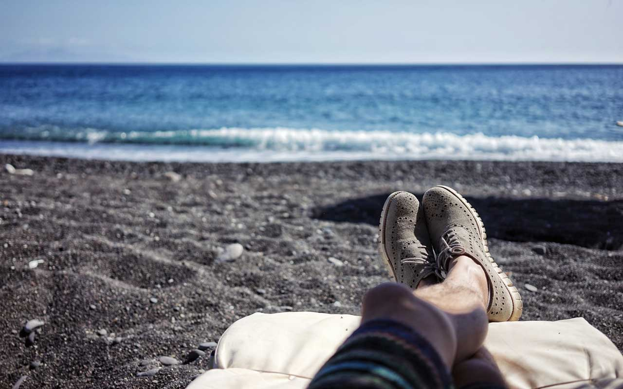 A person relaxes at a black sand beach with their shoes on and legs up.