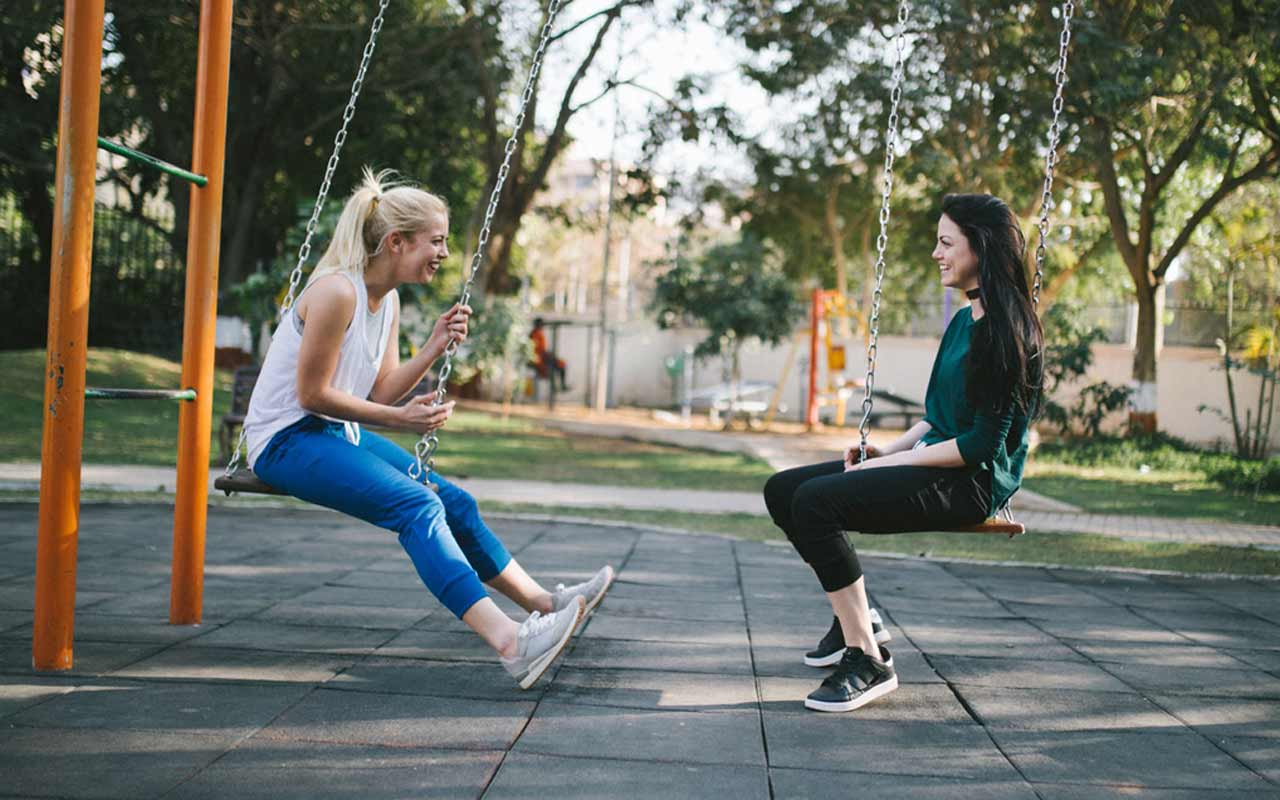 Two women sit on swings outside in a park. Speaking is one of the best ways to learn Spanish quickly.
