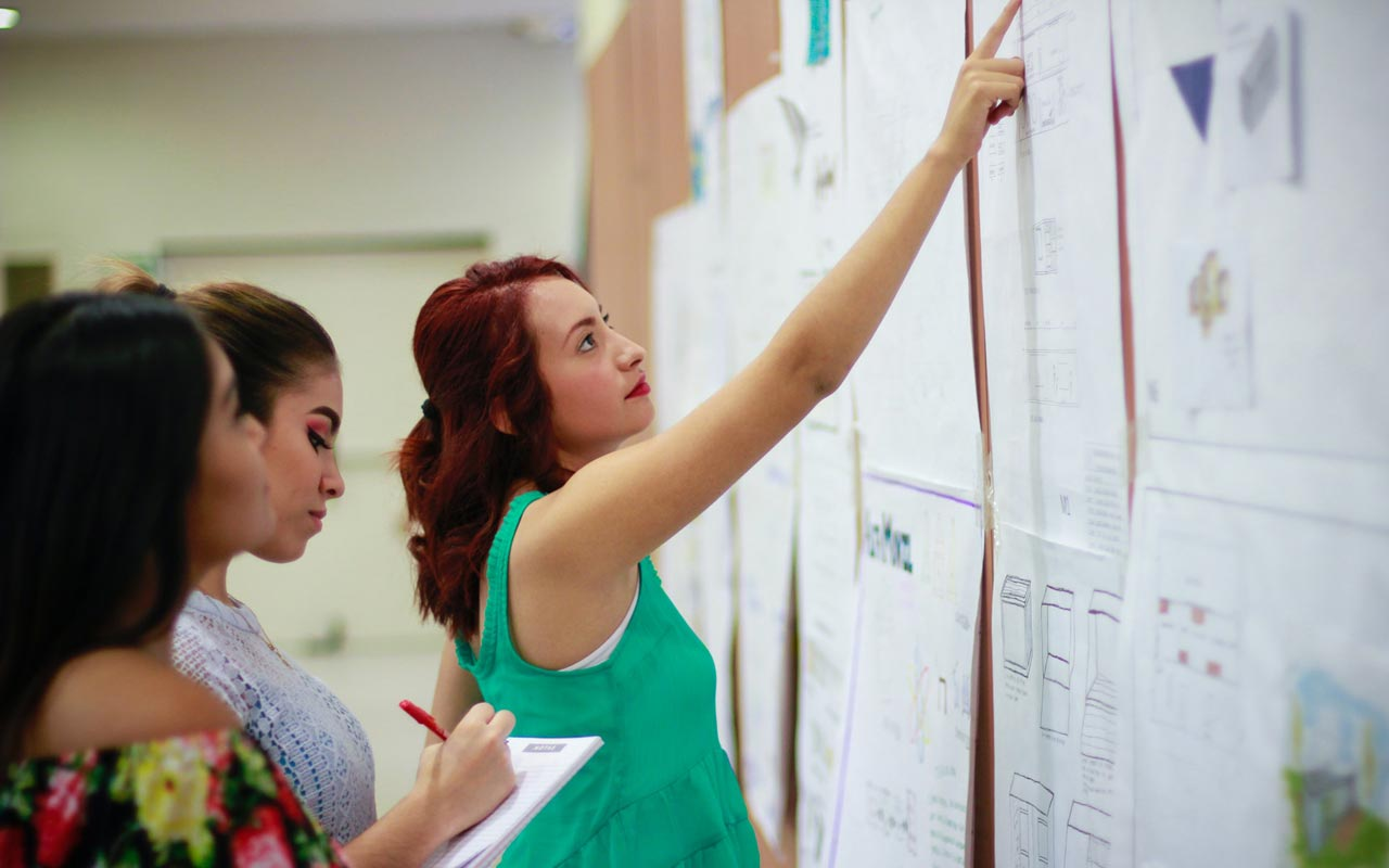 A woman in a green top points at papers on a bulletin board. A good teacher can help you learn Spanish faster.