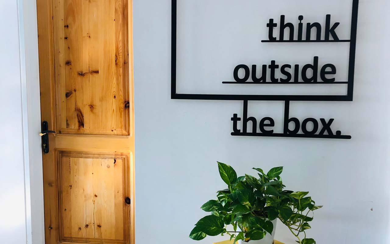 "A sign with the text ""think outside the box"" against a white wall, with a green plant on a table underneath the sign."