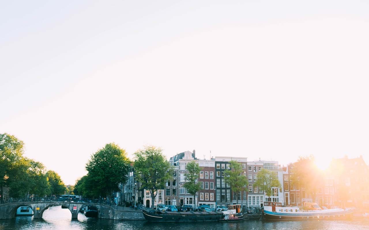 The sun rises over a neighborhood along a canal. The weather is an easy place to start learning Spanish vocabulary.