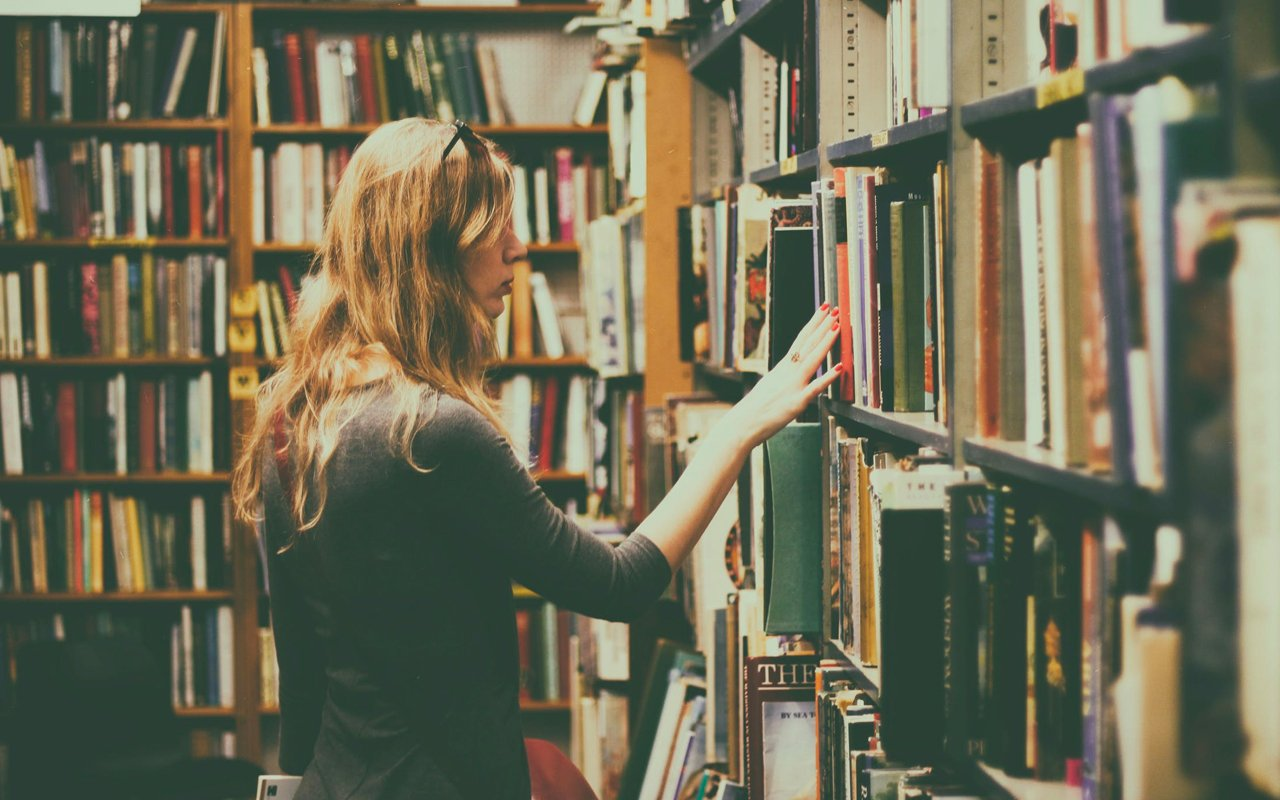 woman selecting books from a shelf