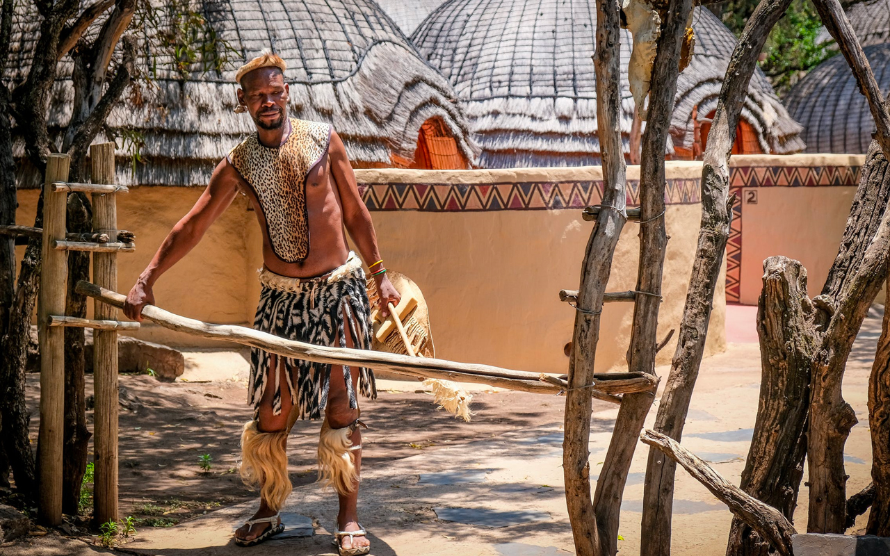 a man in tribal clothes expressing a concept related to cultural and historical knowledge