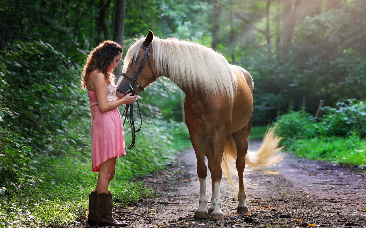 a woman with a horse on the forest path