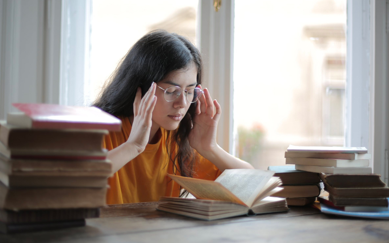 Young woman trying to mind read a book instead of using memory retention strategies