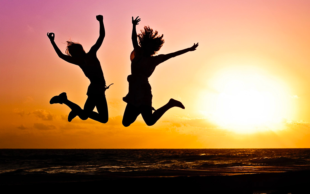 people jumping for joy on a beach