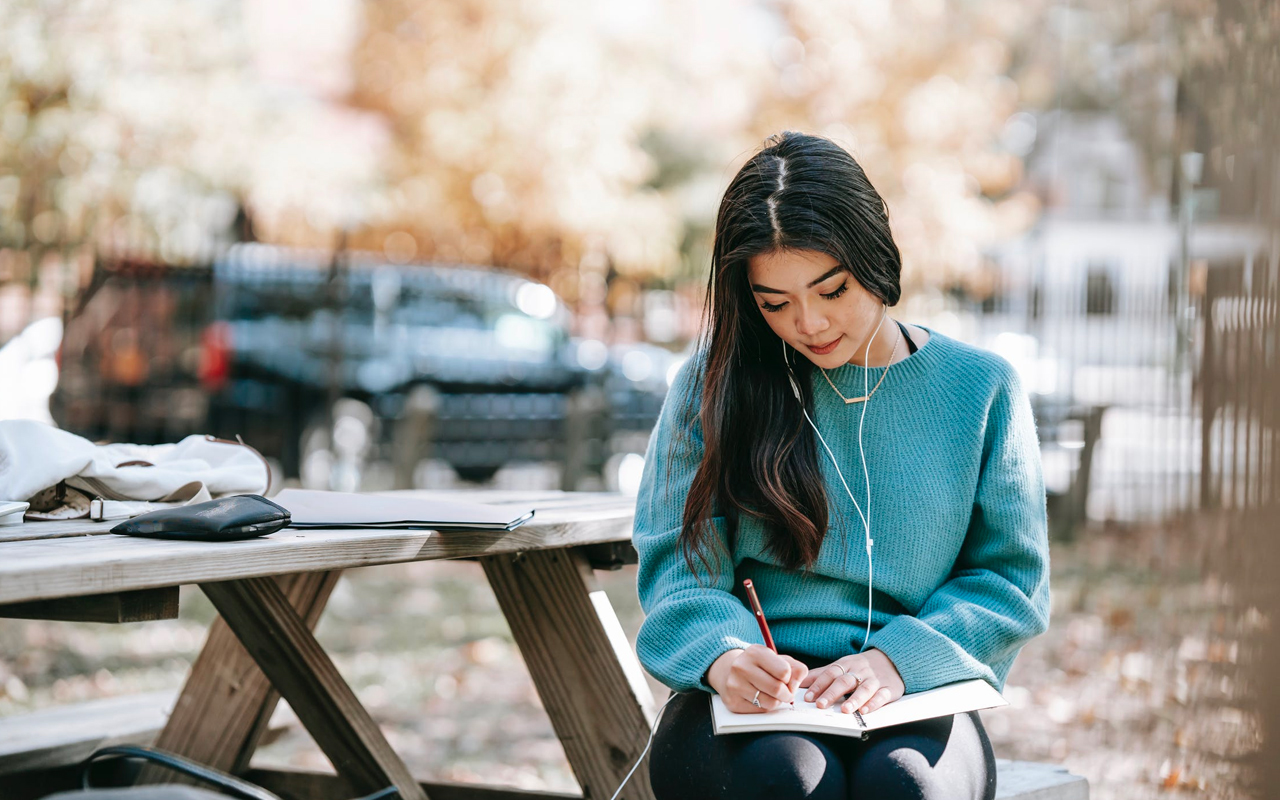 a woman is writing and listening