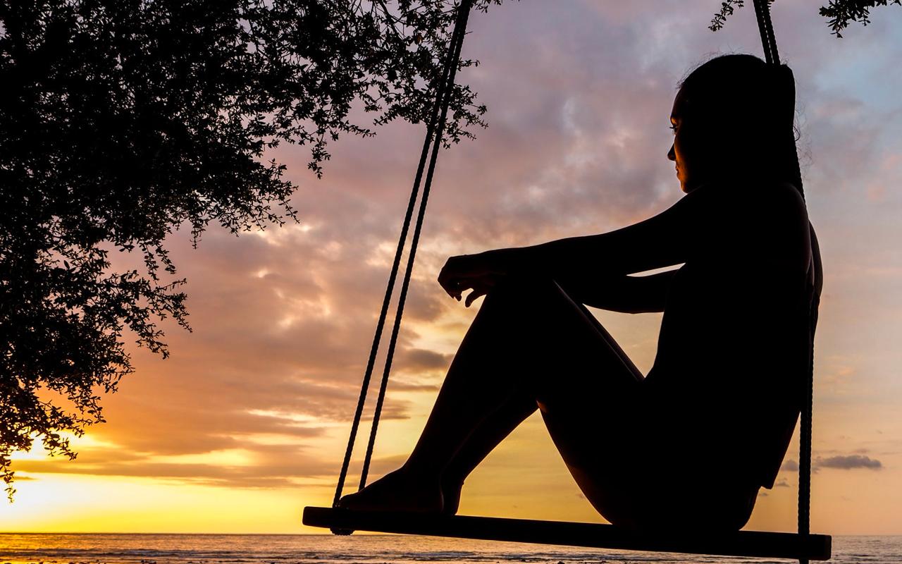 a woman on swing watching sunset