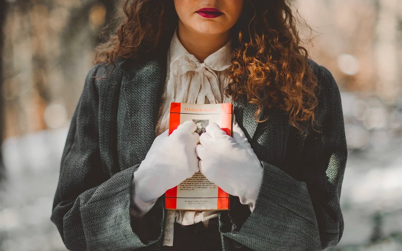 a woman is holding a book on her chest