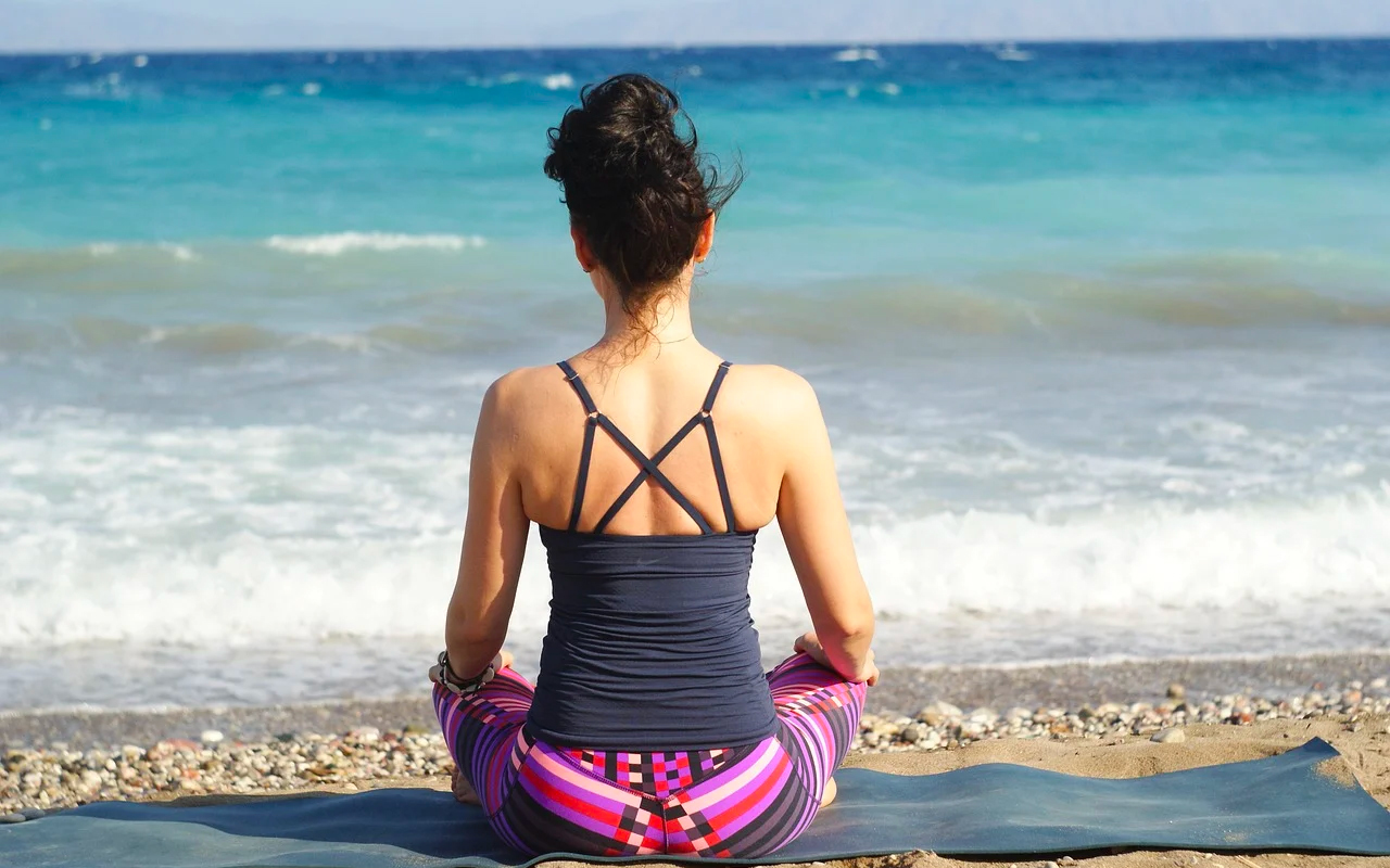 a woman is meditating on a beach