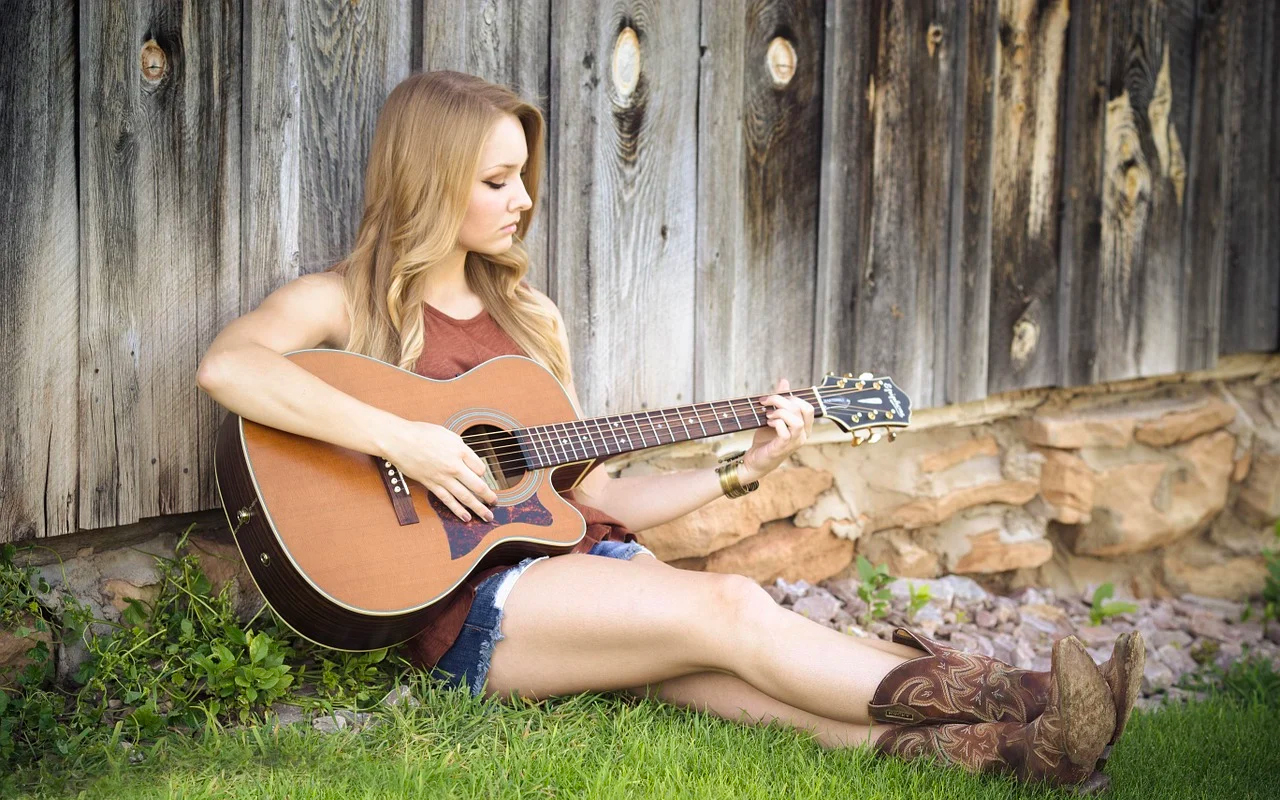 a woman is playing a guitar