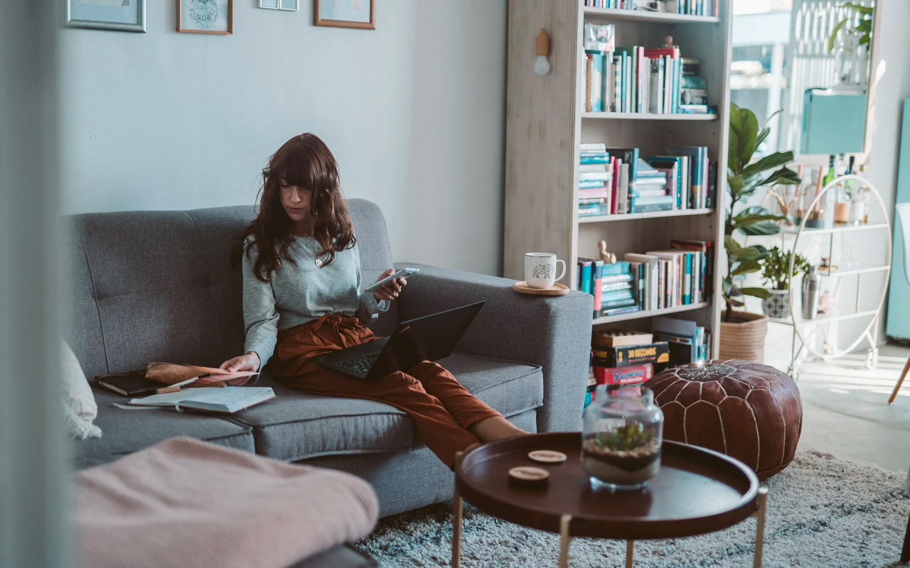 a woman sits on sofa with a book and a laptop