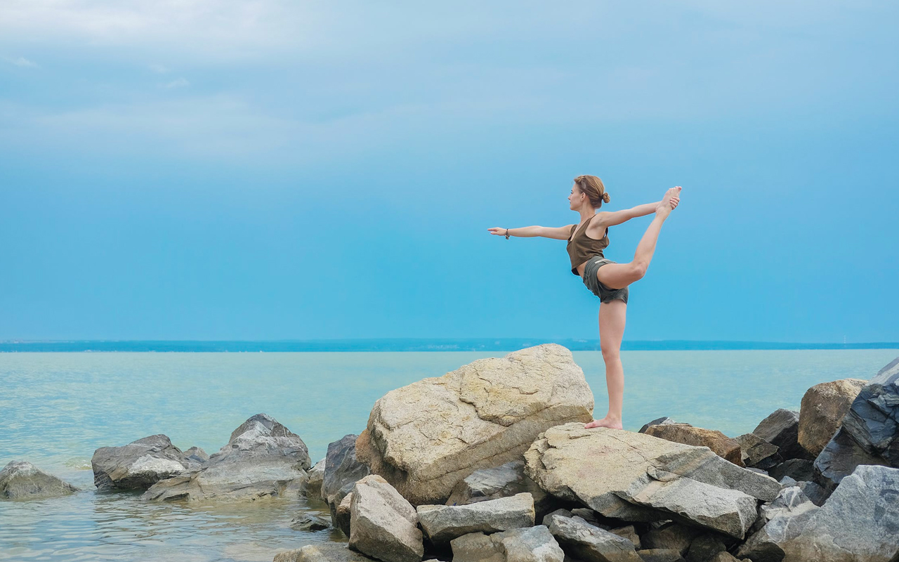 a woman is balancing on rocks