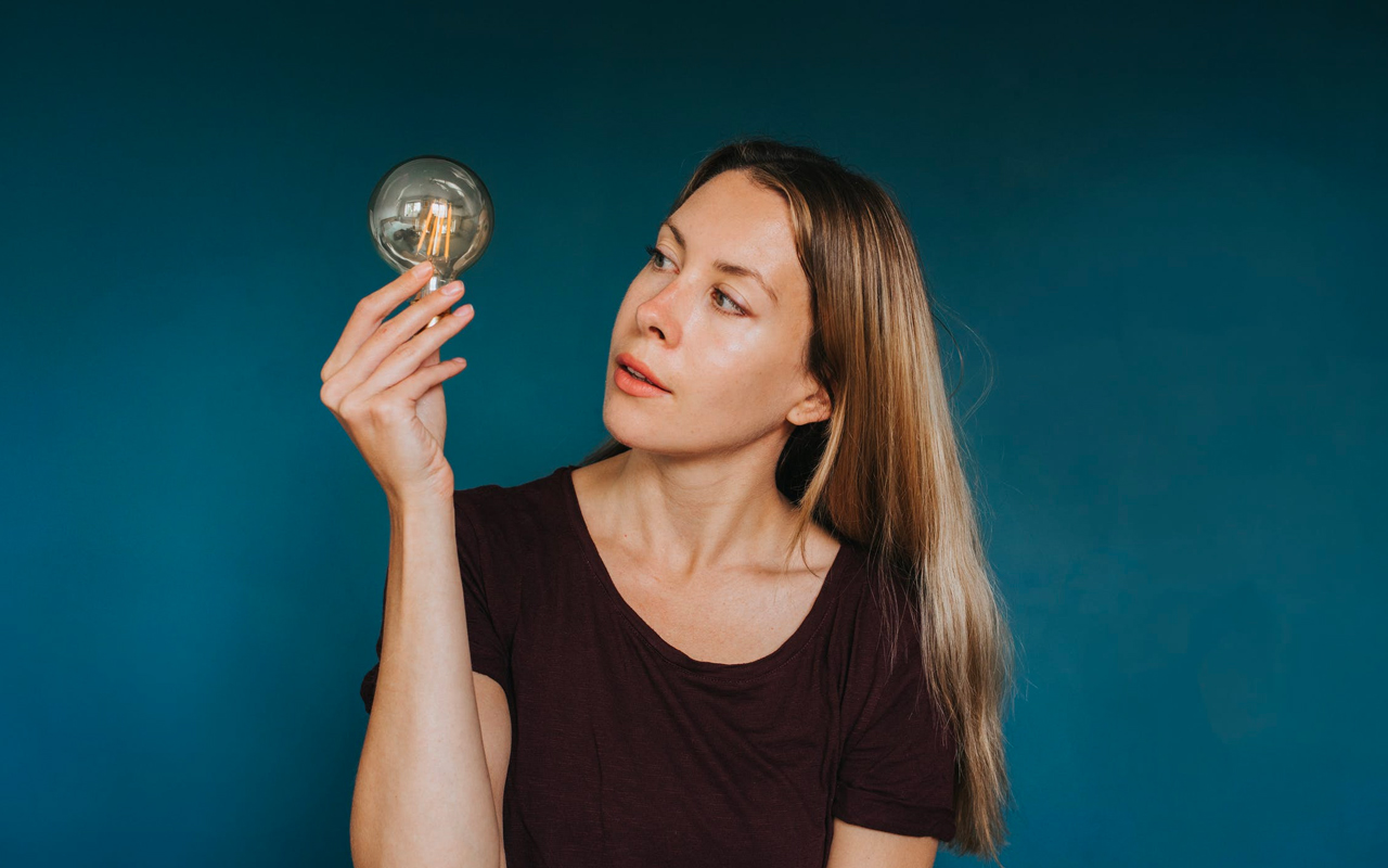 a woman is holding a light bubble