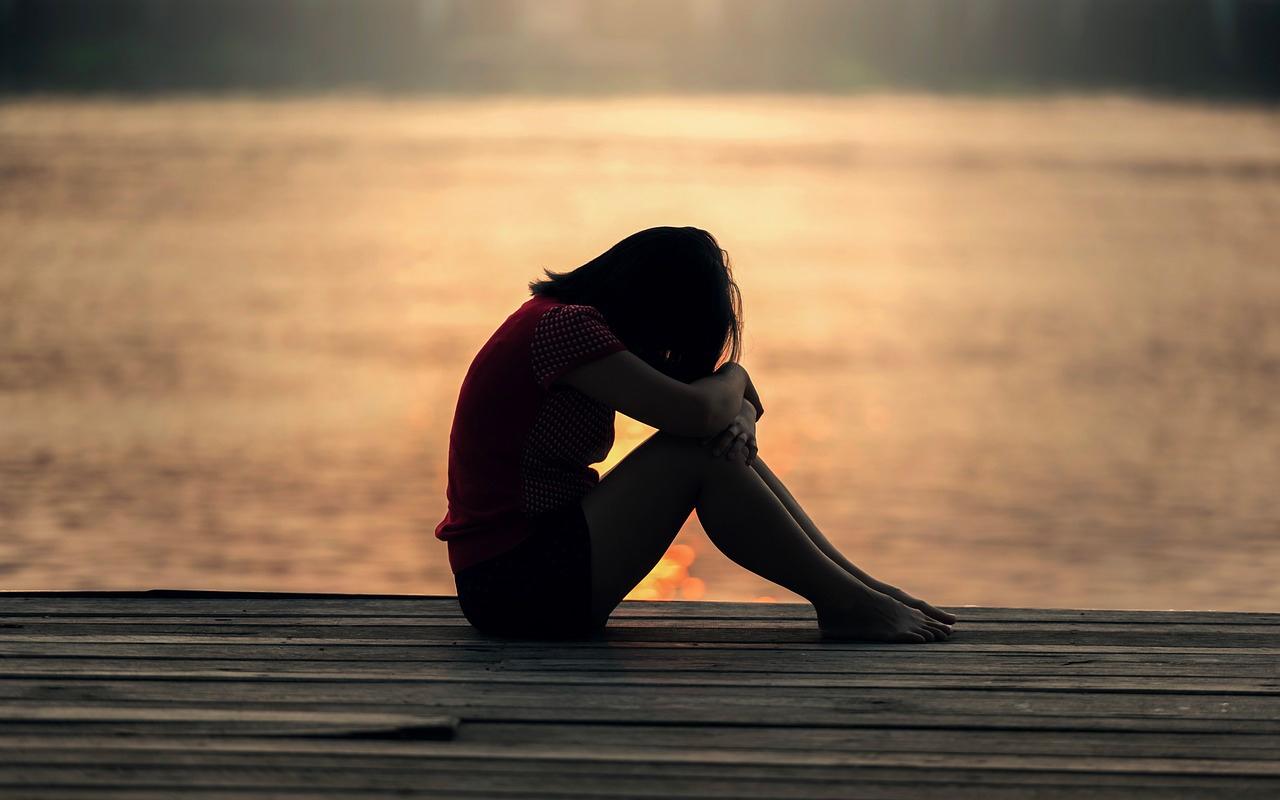 a woman is not happy sitting beside a beach