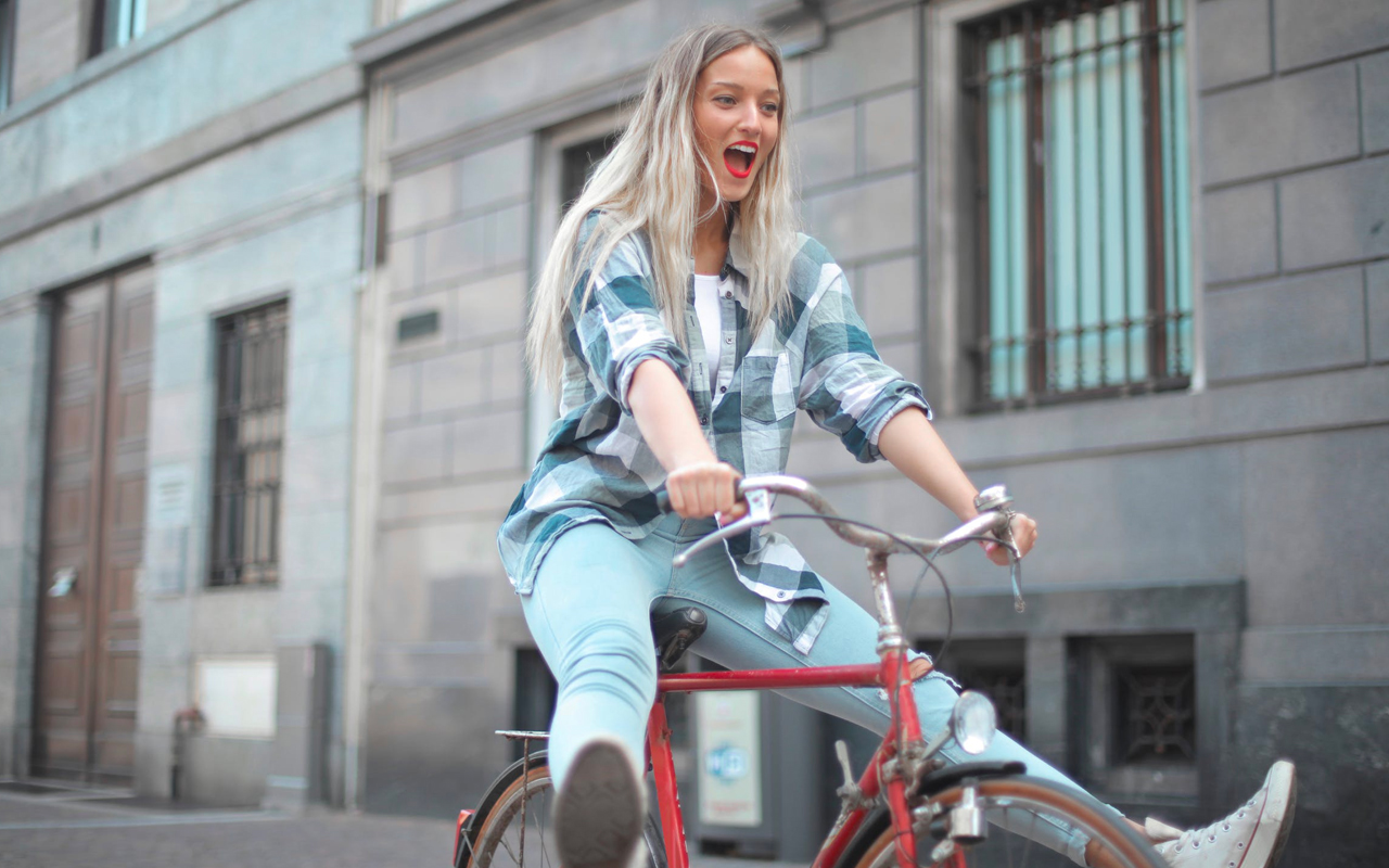 a woman is riding a red bike